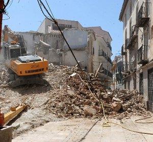 La máquina trabajando en la demolición de una casa en la calle Zorrilla. :: PACO ALONSO / AGM