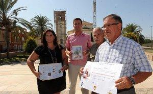 Sandra Martínez, Luis González, el Padre Jerónimo, y Juan Tomás con el cartel de las fiestas delante del Santuario cubierto de andamios. :: P. A. / AGM