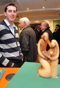 El presidente de los Belenistas con la escultura de roble que preside los carteles y el programa de actividades de esta Navidad. :: P. A. / AGM