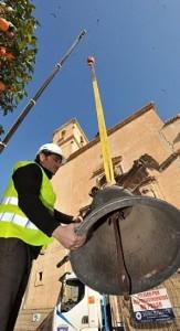 Un obrero coge una de las campanas que bajó una grúa. ::P.A./AGM