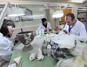 Tres de los expertos contratados por el Instituto de Patrimonio Cultural de España restaurando las piezas dañadas tras los seísmos. :: P. ALONSO / AGM