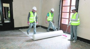 Tres operarios protegen el suelo cerámico del dormitorio principal del Palacio de Guevara antes de iniciar las obras de rehabilitación del monumento. :: SONIA M. LARIO / AGM