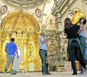 Varios cofrades preparan la lámpara que irá en la cúpula de la capilla para su colocación. :: SONIA M. LARIO / AGM