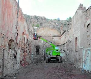 A la izquierda, uno de los técnicos que han participado en el estudio arqueológico encargado por la Concejalía de Obras examina la parte alta de los muros interiores de la ermita de San Lázaro. Arriba, detalle de pinturas murales que se han hallado en una de las hornacinas del monumento. / PATRIMONIO INTELIGENTE